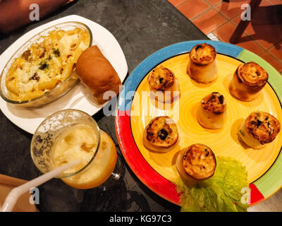 Italian brunch with poppers, lasagna, garlic bread and mocktail drink served on colorful plates - Stock Photo