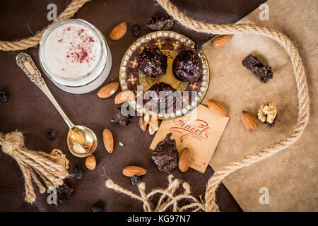 dessert composition coconut cream with strawberries and nuts on a brown background with a decorative lace and chocolate - Stock Photo
