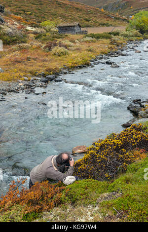 Nature photographer by a creek, Norway - Stock Photo