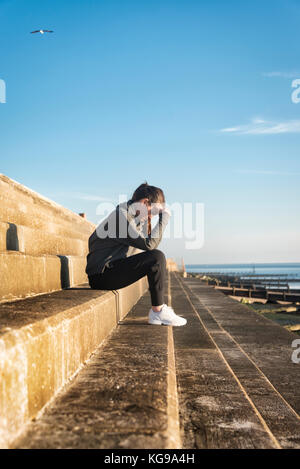 woman sitting on steps outside by the sea with her head in her hands - Stock Photo