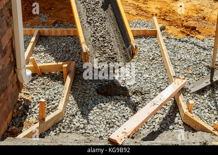Pouring cement during sidewalk upgrade paving concrete pavement near the house - Stock Photo