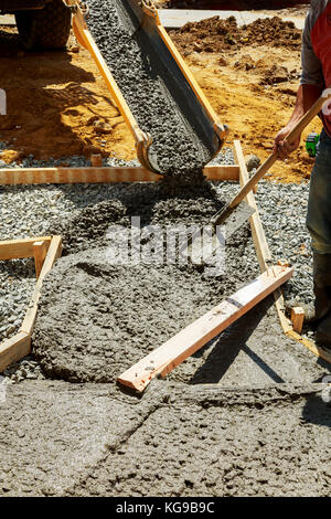 Pouring cement during Upgrade to residential street paving concrete pavement near the house - Stock Photo