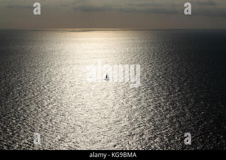 Solitary sailing boat or yacht caught in the sun's reflections on a wide expanse of sea - Stock Photo