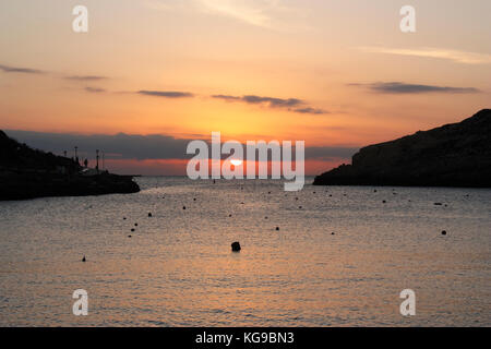 Sunset over the Mediterranean Sea, as seen from the seaside resort of Xlendi in Gozo, Malta - Stock Photo