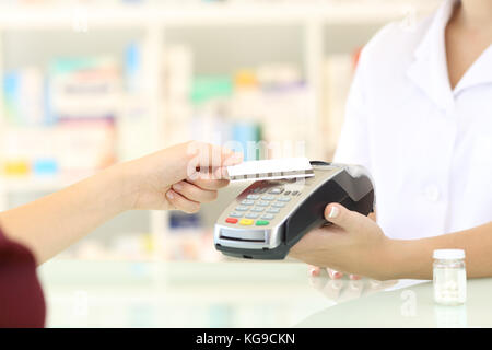 Close up of a customer hands paying with credit card reader in a pharmacy - Stock Photo