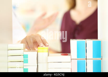 Close up of a pharmacist hands working attending to a customer in a pharmacy interior - Stock Photo