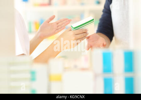 Close up of a pharmacist hands selling medicine to a customer in a pharmacy interior - Stock Photo