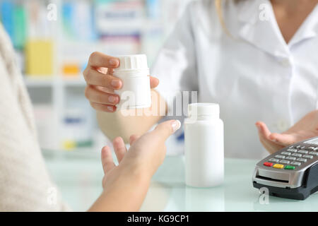 Close up of a pharmacist hands selling medicines to a customer on a pharmacy desk - Stock Photo