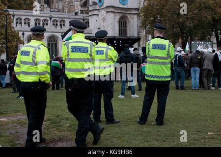 Four policemen overlooking Pro-Palestine protest, London, UK, 4th November 2017 - Stock Photo