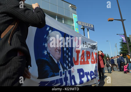 Tokyo, Japan. 5th Nov, 2017. People holds a banner as they welcome the arrival of US President Trump outside Yokota - Stock Photo