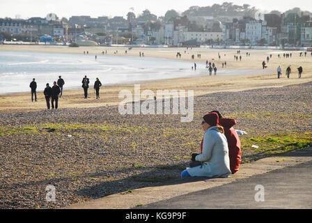 Weymouth, Dorset. 5th November 2017 - People wrap up warm and flock to Weymouth beach to enjoy the autumn sunshine. - Stock Photo