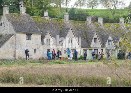 tourists taking photographs outside Arlington Row - a popular row of Cotswold cottages in the pretty Cotswold village - Stock Photo
