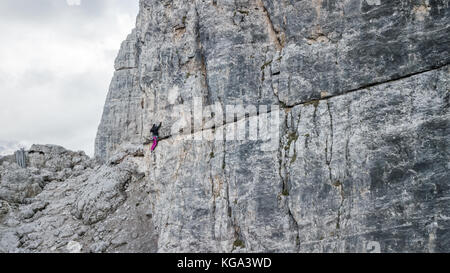 Female rock climber on the Cinque Torri in Cortina D'Ampezzo, Dolomites, Italy. - Stock Photo