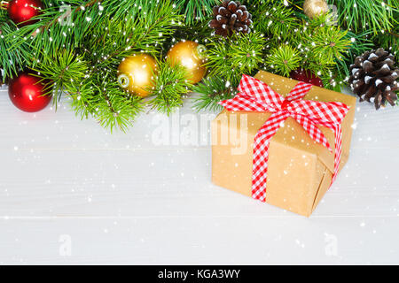 Fir branches with ornaments - gift box, pine cones holly and baubles. Christmas background, copy space - Stock Photo