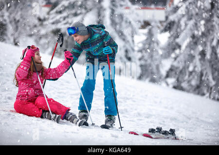 boy learning young girl skiing on snow and having fun - Stock Photo