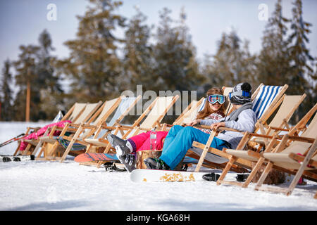 happy children at mountains in winter laughing and relax in sunbed chairs - Stock Photo