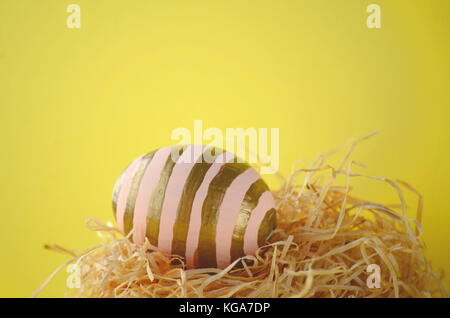Hand painted blush pink Easter egg with gold stripes in a nest on a bright yellow background with copy space. - Stock Photo