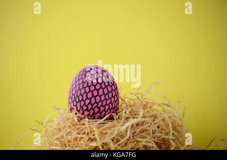 Hand painted pink Easter egg with snakeskin pattern in a nest on a bright yellow background with copy space. - Stock Photo