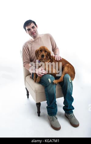 Fair skinned young man seated on chair smiling with his Golden Retriever puppy dog on lap. - Stock Photo