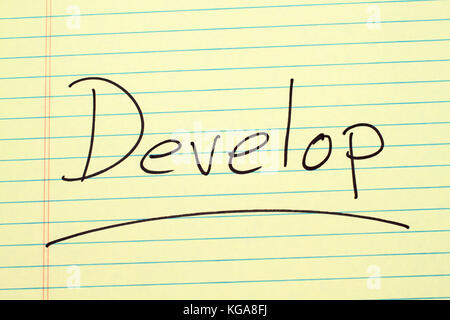 The word 'Develop' underlined on a yellow legal pad - Stock Photo