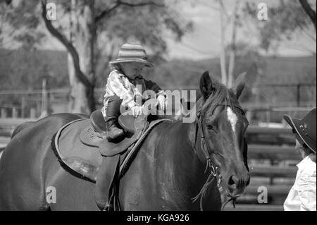 COUNTRY KIDS. LITTLE GIRL ON HORSE - Stock Photo