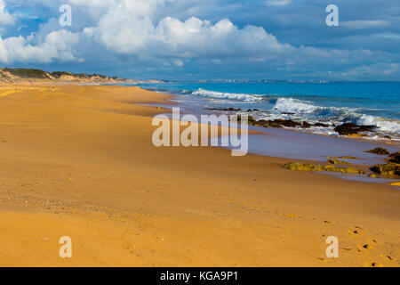 Storm clouds hover over the Indian Ocean at Buffalo Beach near Bunbury Western Australia on a calm late winter afternoon - Stock Photo