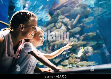 Mother and son watching sea life in oceanarium - Stock Photo