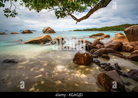 Sailboats, catamarans and granite rocks in the indian ocean on a cloudy day at world famous beach anse lazio, praslin, - Stock Photo