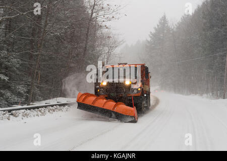 A snow plow clears the road as it snows in Vermont. - Stock Photo