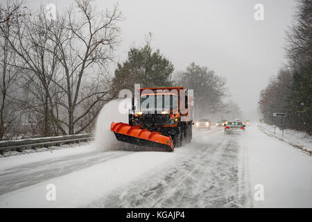 A snow plow clears the road followed by a line of traffic as it snows in Vermont. - Stock Photo