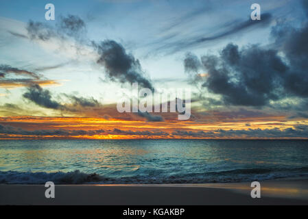 beautiful glowing romantic sunset on paradise beach at anse georgette, praslin, seychelles - Stock Photo