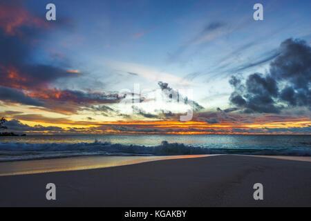 beautiful glowing romantic sunset on paradise beach at anse georgette, praslin, seychelles - Stock Photo