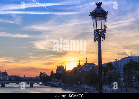 Sunset over Paris, France with Pont des Arts and the river Seine. Colourful skyline with dramatic clouds. - Stock Photo