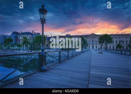 Sunrise over Paris, France with Pont des Arts and Louvre. Beautiful skyline with dramatic sky. Travel and architectural - Stock Photo
