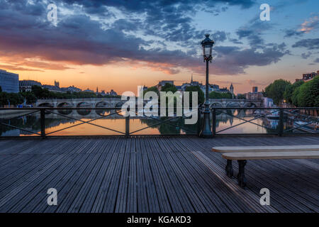 Sunrise over Paris, France with Pont des Arts and the river Seine. Colourful skyline with dramatic clouds. - Stock Photo