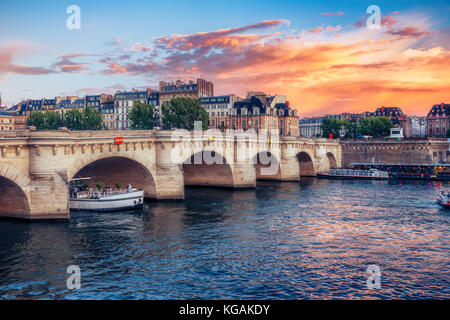 Famous Pont Neuf in Paris, France. Spectacular cityscape with dramatic sunset sky. Travel background. - Stock Photo