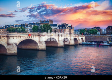 Famous Pont Neuf in Paris, France. Spectacular cityscape with dramatic sunset sky. Travel and architectural background. - Stock Photo