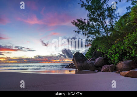 Spectacular romantic purple and orange colored sunset on paradise beach with granite rocks, palm trees sand and - Stock Photo