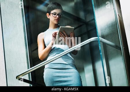 Portrait of attractive young businesswoman using tablet - Stock Photo