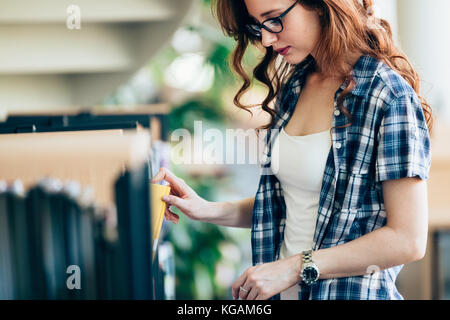 Portrait of young female student in library - Stock Photo