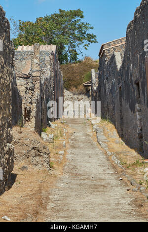 Narrow street among the ruins of houses in Pompeii, Italy in summer time - Stock Photo
