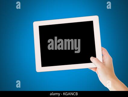 Digital composite of Hand holding tablet with blue background - Stock Photo