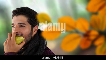 Digital composite of Man's face in forest with leaves eating apple - Stock Photo