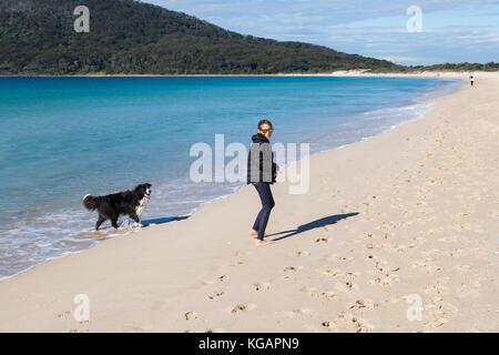 Girl and dog, Hawks Nest, NSW. Australia. - Stock Photo