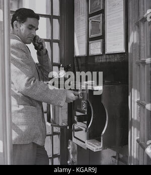Early 1950s, historical picture showing an overseas male visitor to England making a call from a public telephone - Stock Photo
