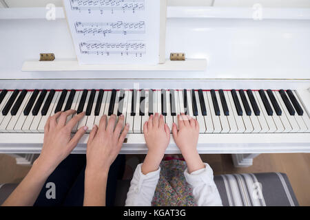 Mid section of mother and daughter playing piano at home - Stock Photo