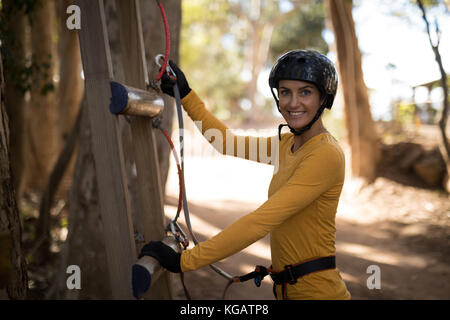 Smiling woman climbing a wooden steps in park - Stock Photo