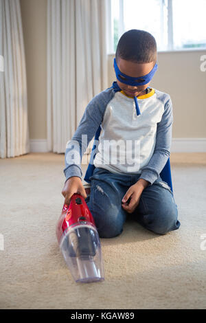 Boy in superhero costume cleaning a floor with vacuum cleaner at home - Stock Photo