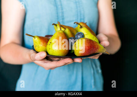 Close up female hands holding plate with summer fruit healthy diet concept - Stock Photo