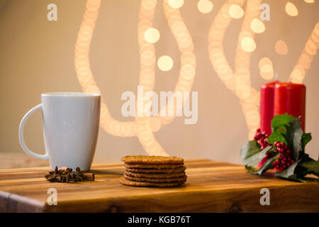 Lovely close up image of Christmas cookies on a wooden chopping board with some scented candles and a glass of whiskey - Stock Photo